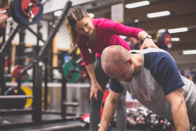 A female personal trainer is helping a man do push ups