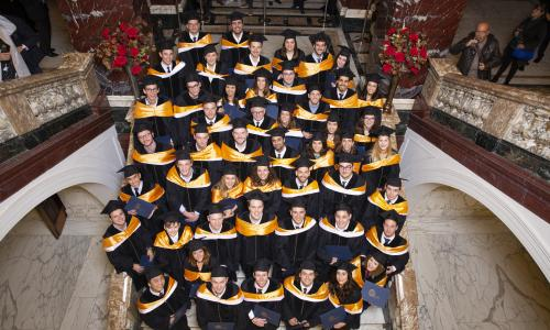Group picture of QTEM graduates dressed in graduation gowns.