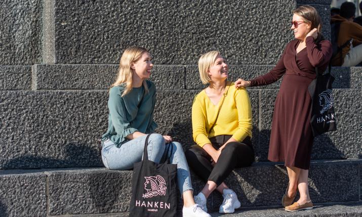 Three women sitting on a statue in Vaasa